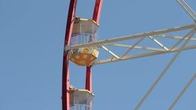 Ferris wheel cabin on the background of blue sky. Ferris wheel close up. People walk near the ferris wheel, a large modern ferris ring. Observation Wheels stock video footage
