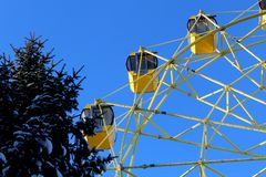 Ferris wheel with cabins closed in winter sunny weather stock images