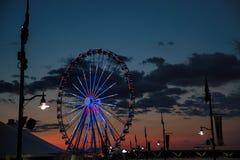 Ferris Wheel capital au port national au coucher du soleil Images stock