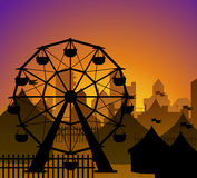 Ferris wheel and circus silhouette. In front of a city in sunset Stock Photography