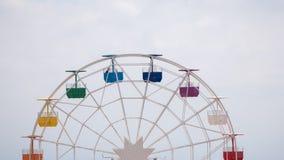 Ferris wheel on cloudy sky background. Rainbow