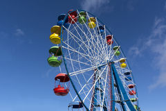 Ferris wheel with colored cabins on the blue sky background, Sun Stock Photos