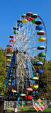 Ferris wheel with colored cabins in the park Stock Photo