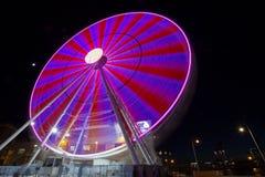 Ferris wheel with colored lights in `Porto Antico` harbor zone in Genoa, Italy stock photography