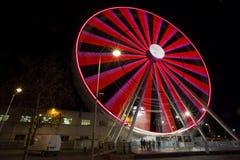 Ferris wheel with colored lights in `Porto Antico` harbor zone in Genoa, Italy stock photo