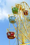 Ferris wheel with colorful colorful booths in the amusement Park against a bright blue sky