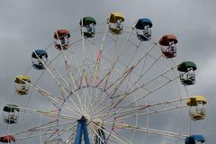 Ferris wheel with colorful booths in the amusement Park on the background of the stormy sky royalty free stock photography
