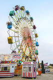 Ferris Wheel. A colorful ferris wheel with enclosed, spinning cars entertains visitors at a carnival Stock Image
