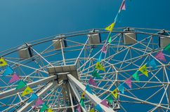 Ferris wheel and colorful flags in the amusement Park against th stock photos