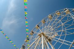 Ferris wheel and colorful flags on blue sky background stock photography