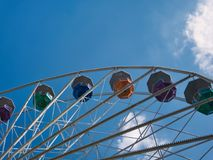 Part of a ferris wheel with colorful gondolas stock photography