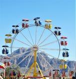 Ferris Wheel colorido contra o ajuste do céu azul e da montanha imagens de stock royalty free
