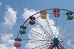 Ferris wheel colors against white clouds on bright summer day Royalty Free Stock Photos