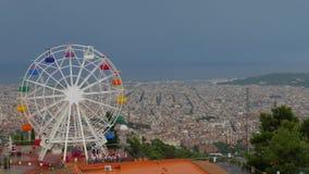 Ferris Wheel contra el cielo gris y el panorama hermoso de Barcelona almacen de video
