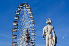 Ferris wheel in the deep blue sky with a statue beside Royalty Free Stock Photo