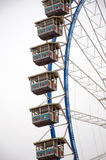 Ferris wheel detail and cabins in a cloudy sky and white. For fun moments stock photography