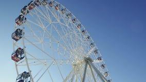 Ferris Wheel escena Rueda de la observación - cierre encima del tiro Ferris Wheel Spinning en el fondo de un cielo azul almacen de video
