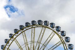 Ferris Wheel At The Fairground Over Blue Cloudy Sky. In Background Stock Photos