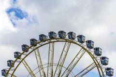 Ferris Wheel At The Fairground sobre o céu nebuloso azul fotos de stock