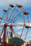 Ferris wheel funfair ride. With sign against blue daytime sky royalty free stock photography