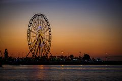 Ferris wheel and Georgian alphabet tower on orange sunset background. Silhouettes of the wheel and tower in the evening in the lights of illumination with the stock photo