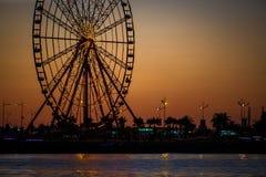 Ferris wheel and Georgian alphabet tower on orange sunset background. stock photography