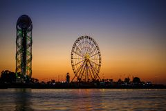 Ferris wheel and Georgian alphabet tower on orange sunset background. Silhouettes of the wheel and tower in the evening in the lights of illumination with the royalty free stock photos