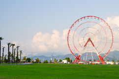 Ferris wheel on green field, mountains, palms and blue sky with light clouds in Batumi, Georgia Royalty Free Stock Photos