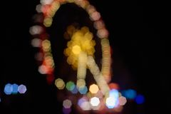 Ferris wheel with illumination. Blurred night background of ferris wheel with illumination for Christmas stock photography