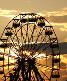 Ferris Wheel landscape with the sun setting behind it. A golden sunset sky landscape with a ferris wheel in the foreground Stock Image