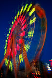 Ferris wheel in motion. Blurry motion of Ferris Wheel in night park stock photography