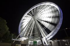 Ferris Wheel in motion glowing at night Stock Photos