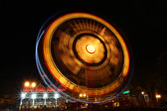 Ferris Wheel in motion illuminated at night Stock Photos