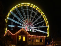 Ferris wheel in motion in Theme Park at night. The blurred illustration of a spinning Ferris wheel in the background of a festive decorated building. Night scene Royalty Free Stock Image