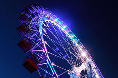 Ferris wheel with multi-colored illumination against the dark bl Stock Photo