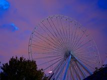 Ferris Wheel Night. Ferris wheel at night in an amusement park. The clouds and sky are a cool purple and blue hue Stock Photos