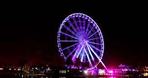 Ferris Wheel at night. Illuminated Ferris Wheel running along waterfront of Montreal, Quebec, Canada at night stock footage