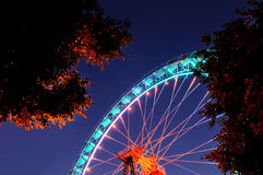 Ferris wheel with orange and light blue illumination with trees. Royalty Free Stock Image