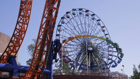 Ferris wheel and other rides in the amusement Park. Time Lapse. HELSINKI, FINLAND - JUNE 07, 2016: Ferris wheel and other rides in the amusement Park Linnanmaki stock video footage