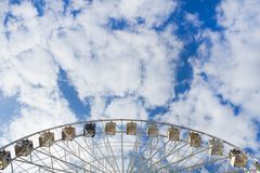 Ferris wheel over the blue sky. The Ferris wheel pleases the sky with clouds. Summer. City royalty free stock photo
