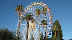 Ferris wheel and palm trees against the sky in Nice. Timelapse of Christmas Ferris wheel and palm trees in Albert I Garden, Nice, France, on a sunny winter day stock video