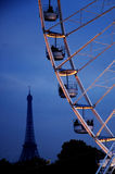 Ferris wheel in Paris. Ferris wheel illuminated at night with view of Eiffel Tower in background stock photography
