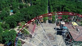 Ferris wheel in the park, aerial view. A large ferris wheel in the middle of a green park filming with a drone. Ferris wheel in the park. Aerial view. A large stock footage