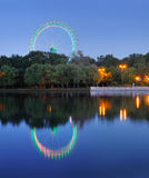 Ferris wheel in the park with colored illumination and reflectio Royalty Free Stock Photos