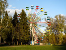 Ferris wheel in the park of the Ukrainian city of Sumy. Carousel for children and adults on a clear sunny day - bright photo Stock Images