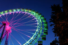 Ferris wheel with pink and green illumination against the dark b Stock Photos