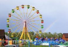 Ferris wheel and rainbow at an amusement park. Royalty Free Stock Image