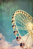 Ferris wheel retro. Retro style image of a ferris wheel against blue sky. Cross-processed, grunge effect Stock Images