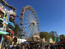Ferris Wheel, roligt hus och uppfriskningställningar på en fullsatt tysk rolig mässa royaltyfri bild