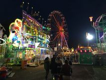 Ferris Wheel, roligt hus och uppfriskningställningar på natten på den tyska roliga mässan royaltyfri fotografi